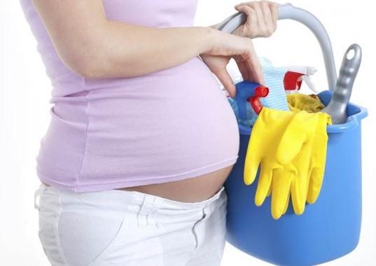 Gravid kvinne med rengjøringsprodukter